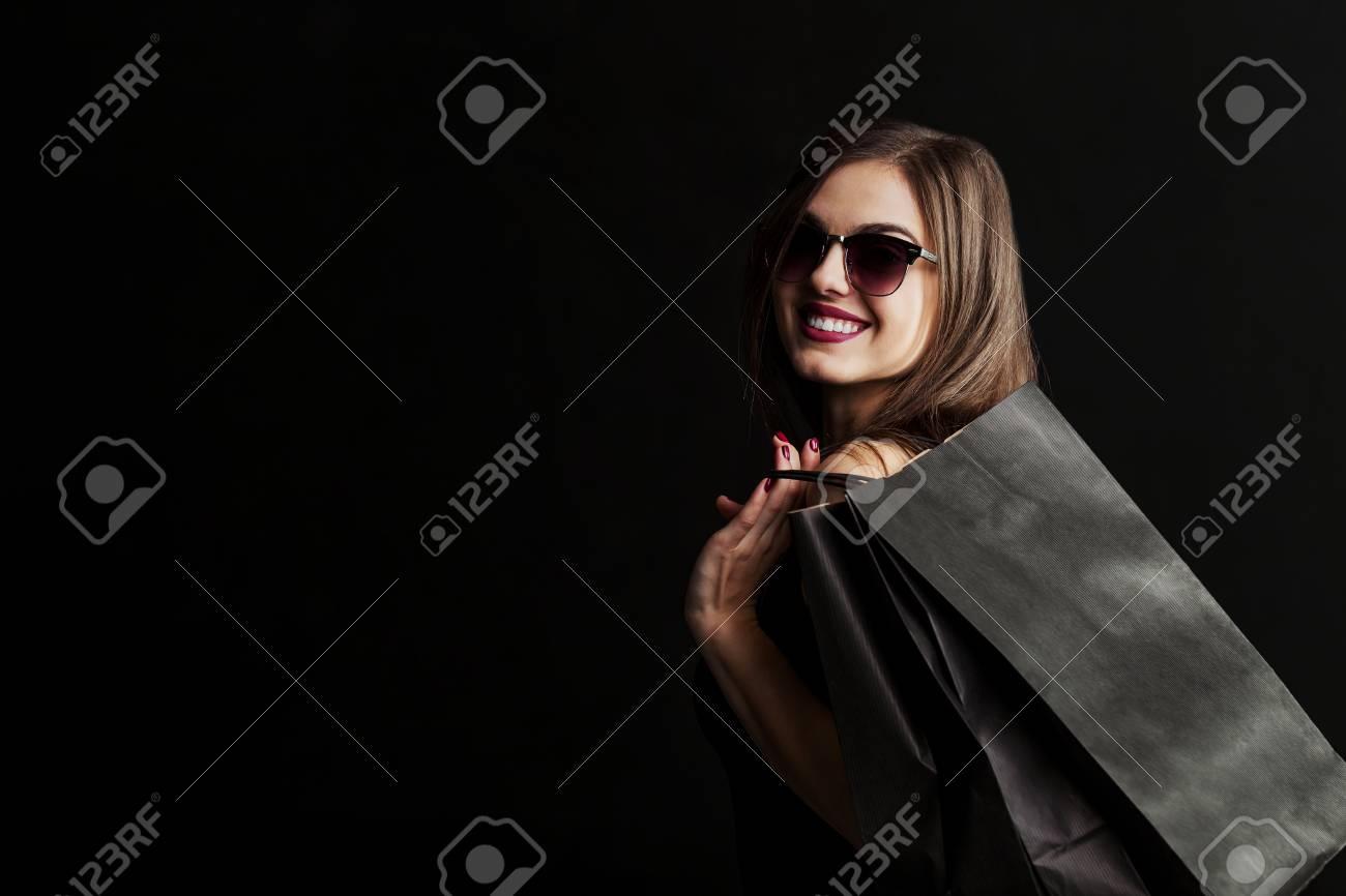 Elegant brunette woman wears sunglasses and black dress holding black shopping bags, black friday concept - 89135962