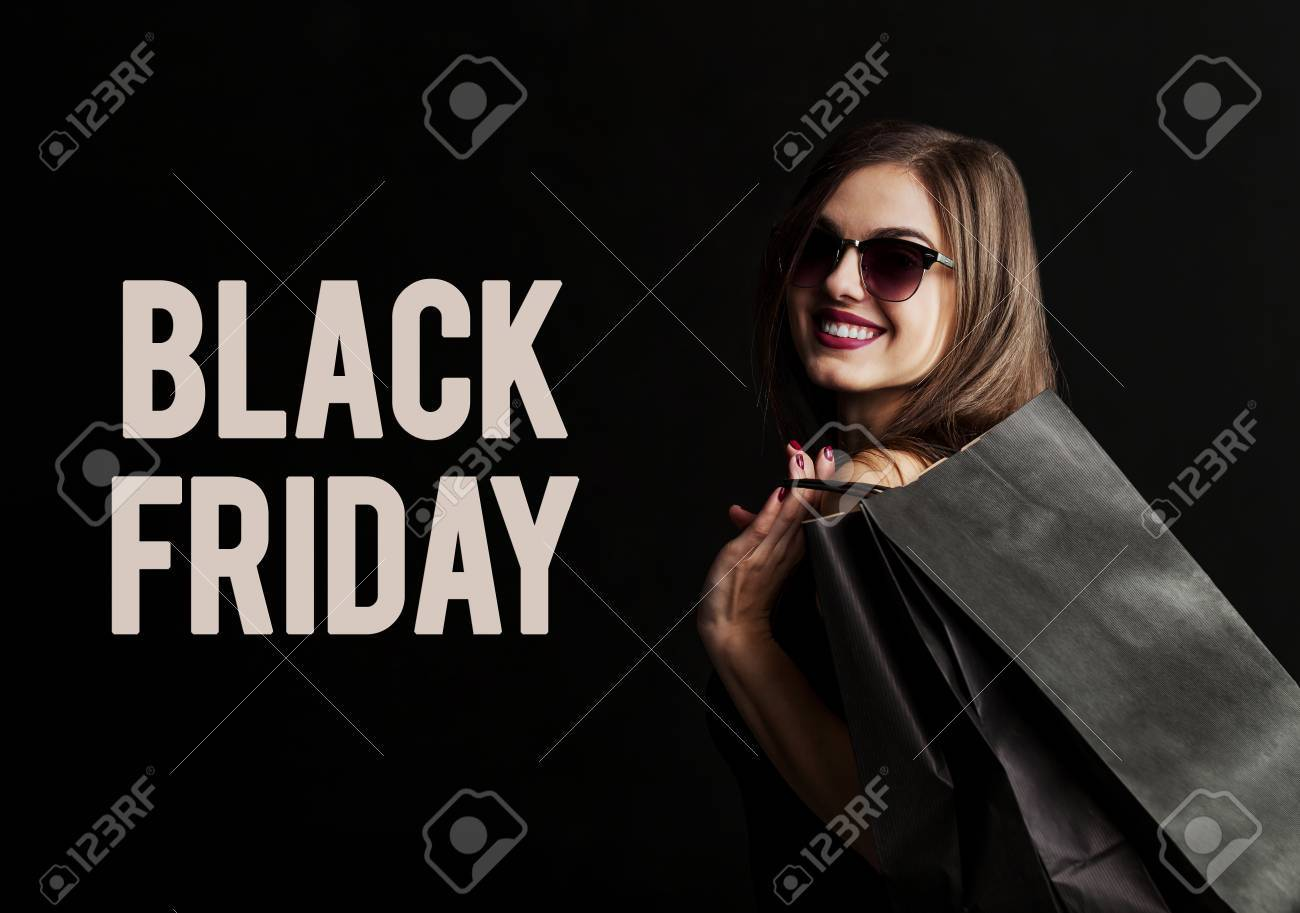 Elegant brunette woman wears sunglasses and black dress holding black shopping bags, black friday concept - 89136013