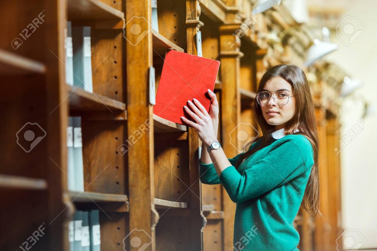 Slender brunette wearing stylish glasses and green sweater holds red book near library bookshelves - 98224634