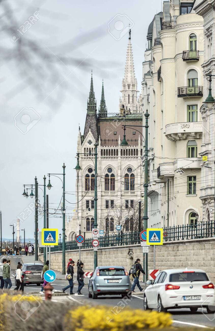 BUDAPEST, HUNGARY - 24 August, 2018: Spring view on the Hungarian Parliament Building of the urban street with cars and people - 137706403