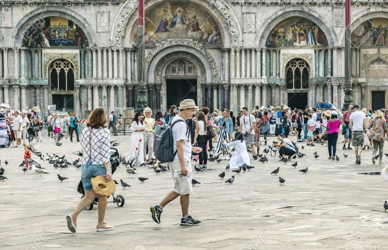 VENICE, ITALY - 25 August, 2018: St Marks Square in Venice with many tourists and pigeons on a spring warm day - 137706418