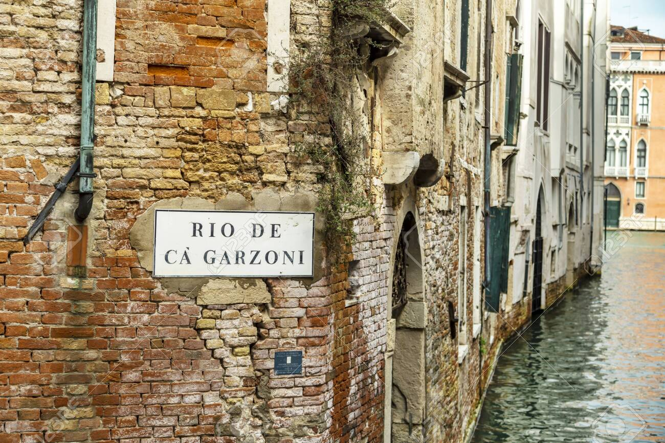 VENICE, ITALY - 25 August, 2018: View of the Rio de Garzoni Canal and brick wall of ancient building in Venice, Italy - 137706420
