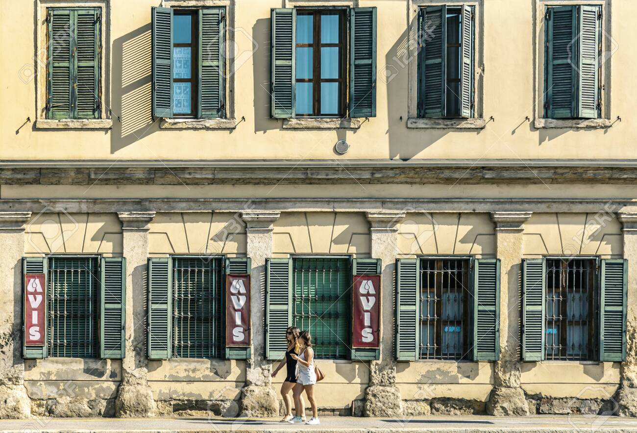 VERONA, ITALY - AUGUST 26, 2018: Symmetrical view on a fasad of house in Verona, people walking on the street - 137706640