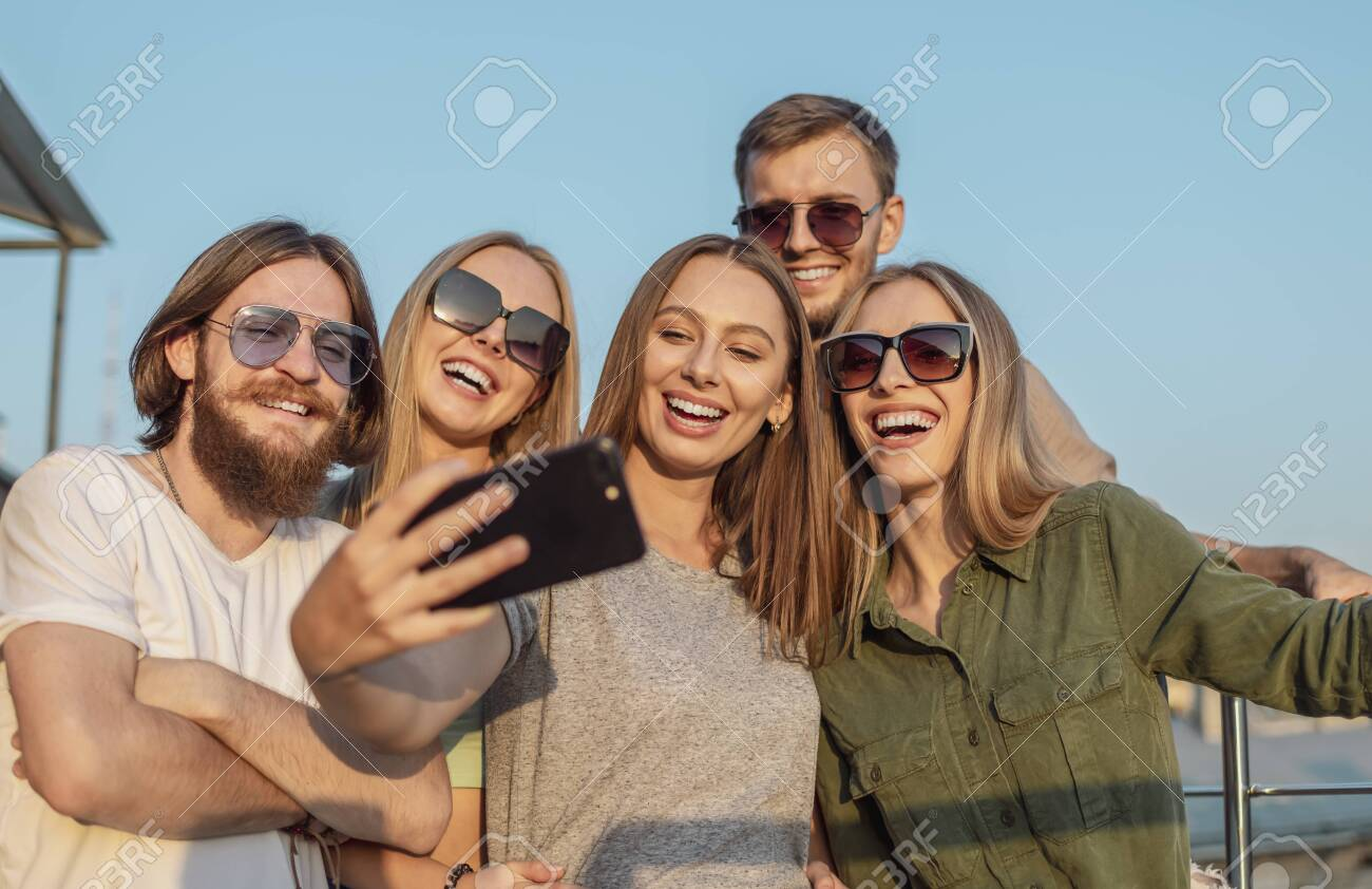 Joyful pals photograph themselves on the edge of a balcony lit by sunset sun - 145147738