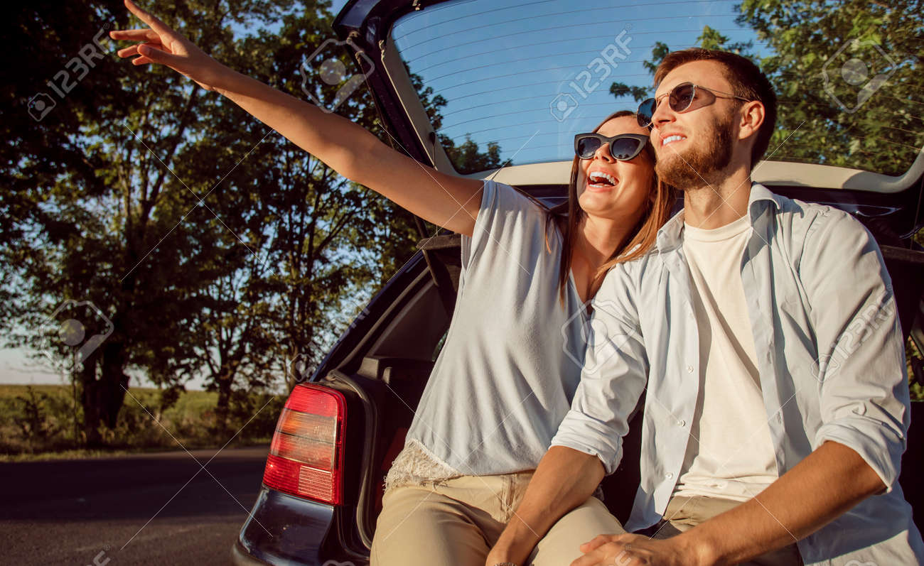 Young cheerful couple admires the countryside views while sitting in the car trunk in the rays of sunset sun - 145147751