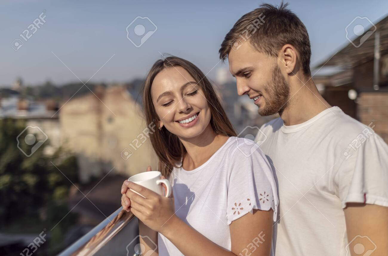 Young cute couple enjoys the view while having coffee on a summer balcony - 145147817