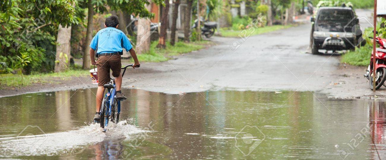 Lake Batur Bali January 21 Kid Cycling Through Flooded Street