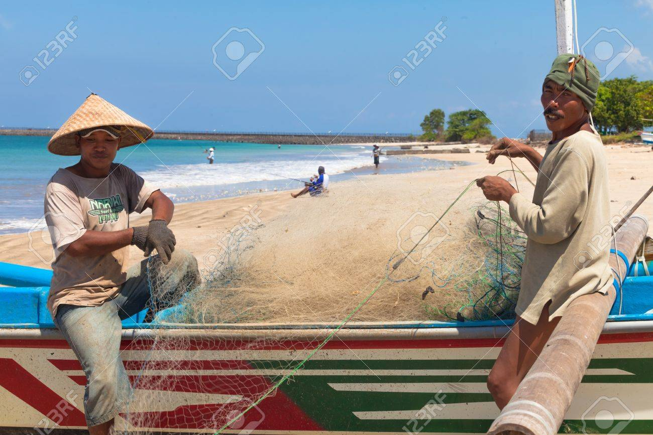 BALI - FEBRUARY 13. Fishermen cleaning nets on beach on February 13, 2012 in Bali, Indonesia. Fisheries Minister Fadel Muhammad said Indonesia set to become world's largest fish producer in 2015. Stock Photo - 13669975