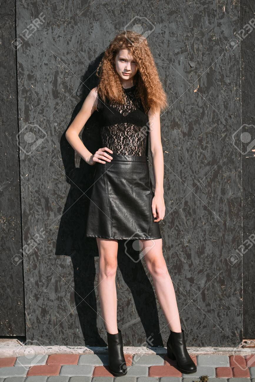Red-haired girl in a black dress near a dark textured wall. - 151332796