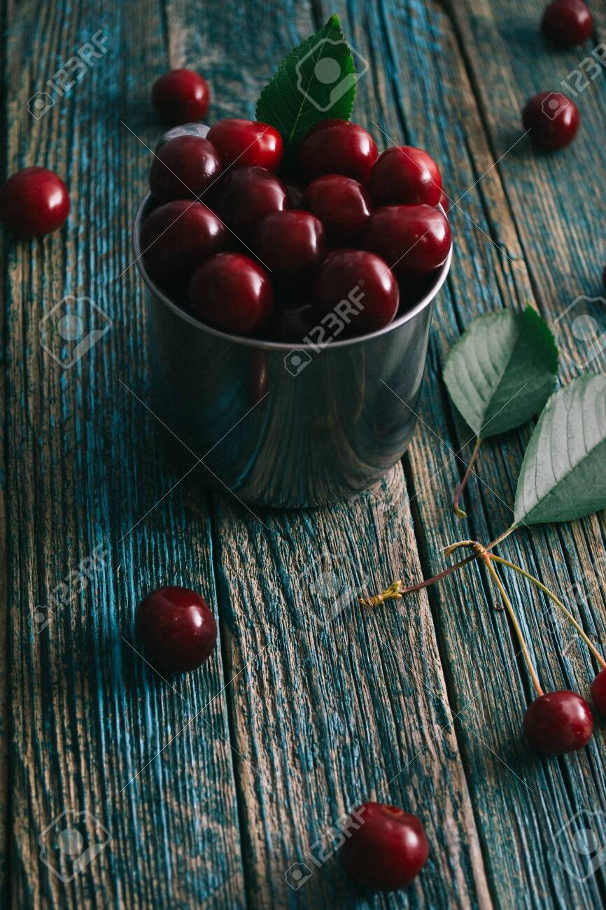Cherries in a steel mug on a wooden background. - 151332805