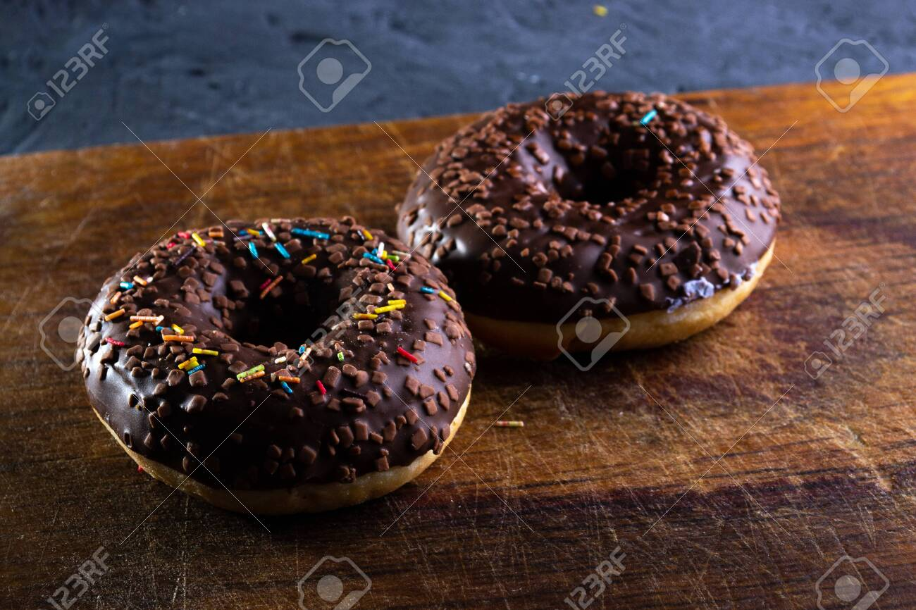 Donuts on a wooden board on a blue concrete background. - 151261064