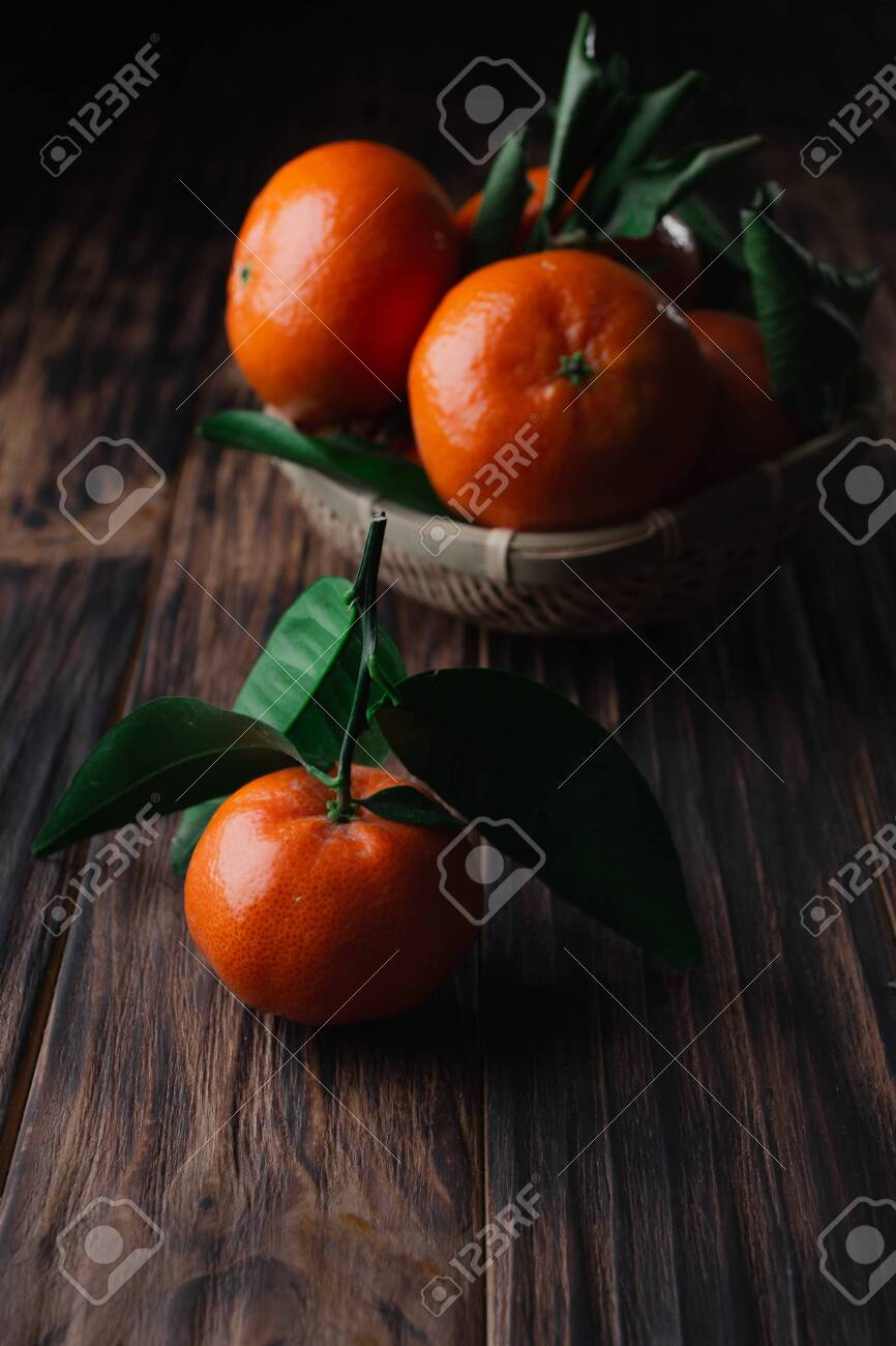 Fresh tangerines with leaves on a wooden old background. - 151260976
