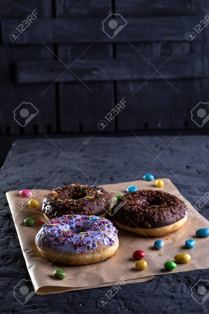 Donuts on a wooden board on a blue concrete background. - 151260936