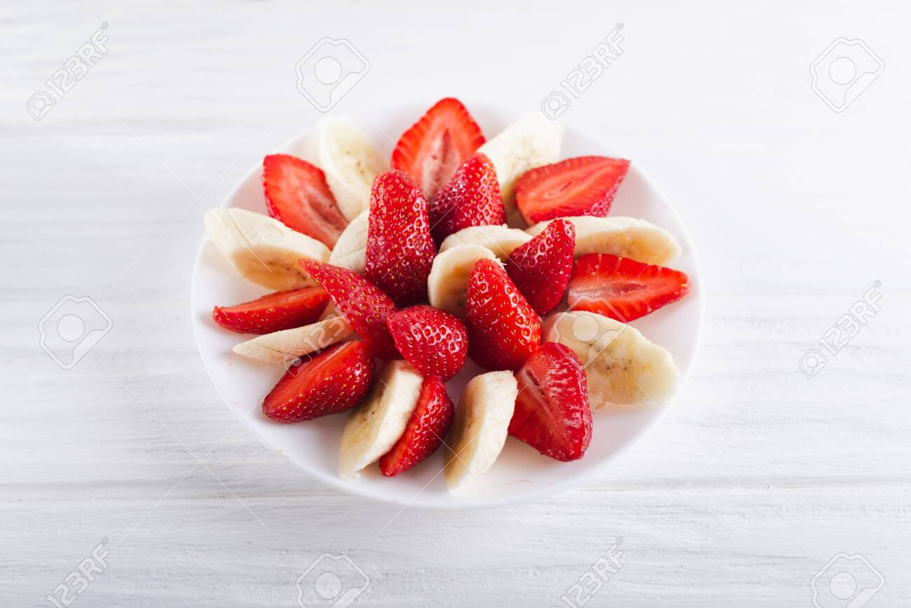 Juicy fresh sliced strawberries with banana on a white plate on a white wooden background. - 151404076