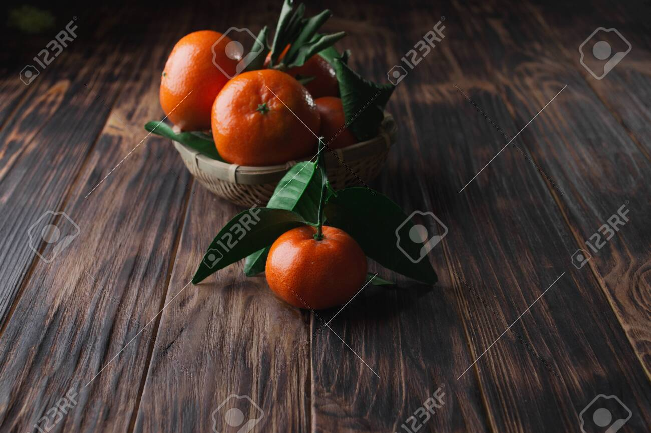 Fresh tangerines with leaves on a wooden old background. - 151402270