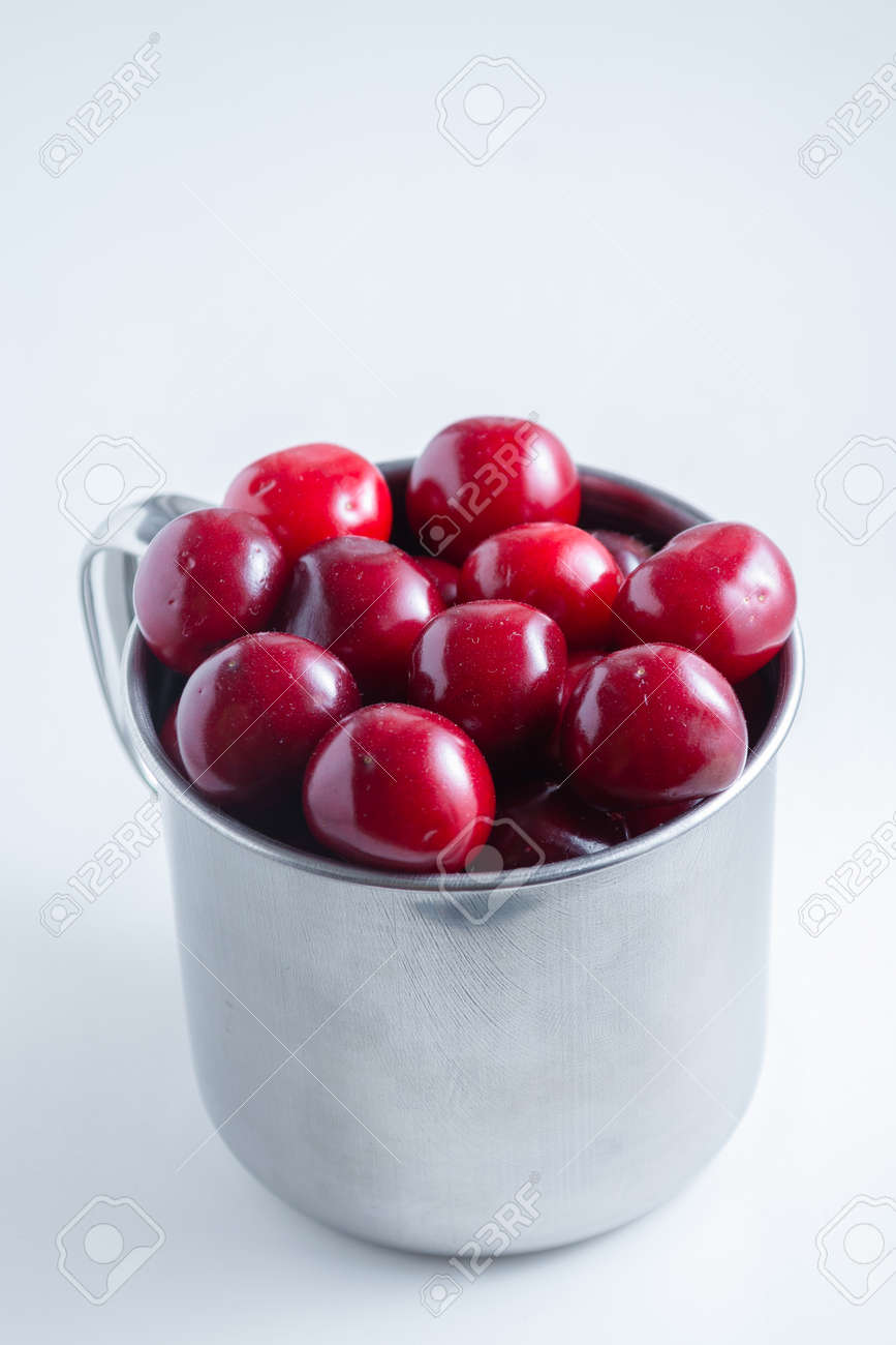 Sweet cherries in a steel mug on a white paper background. - 151404131