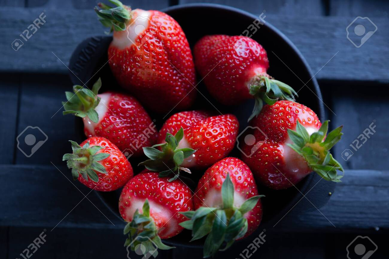 Fresh ripe strawberries on a black wooden background. - 151402324