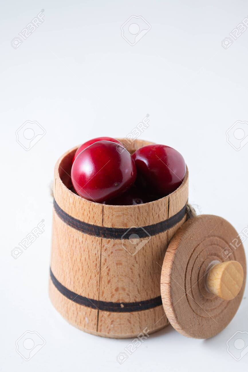 Sweet cherry berries in a wooden small barrel on a white background isolate. - 151404140