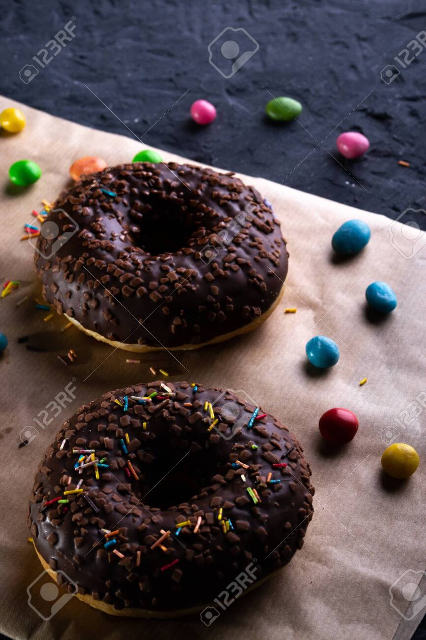 Donuts on a wooden board on a blue concrete background. - 151402407
