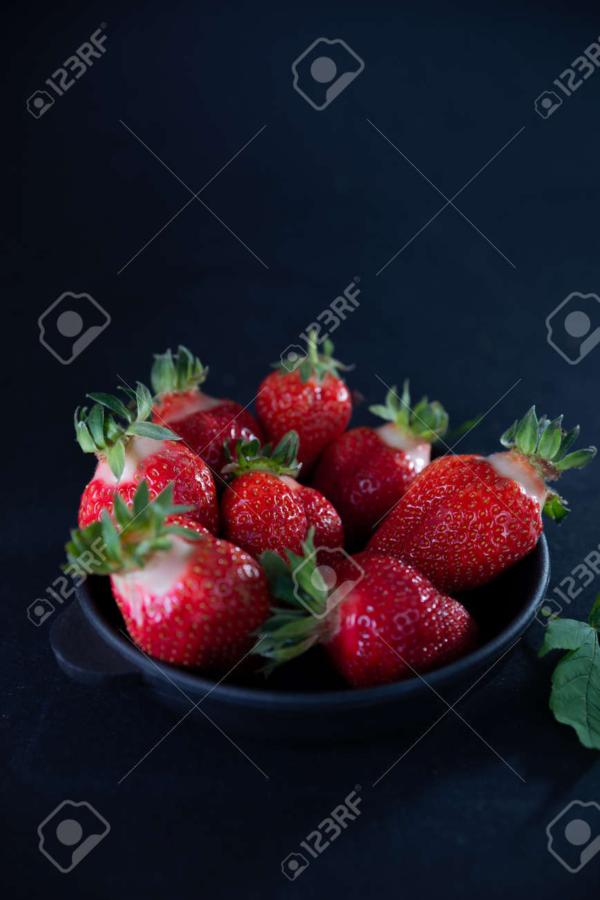 Fresh juicy strawberries in a black plate on a black matte background. - 154902150