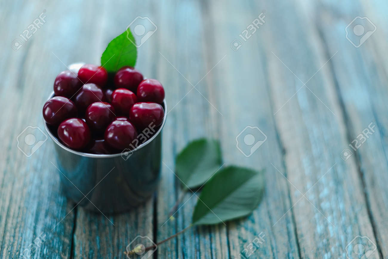 Cherries in a steel mug on a wooden background. - 154903168