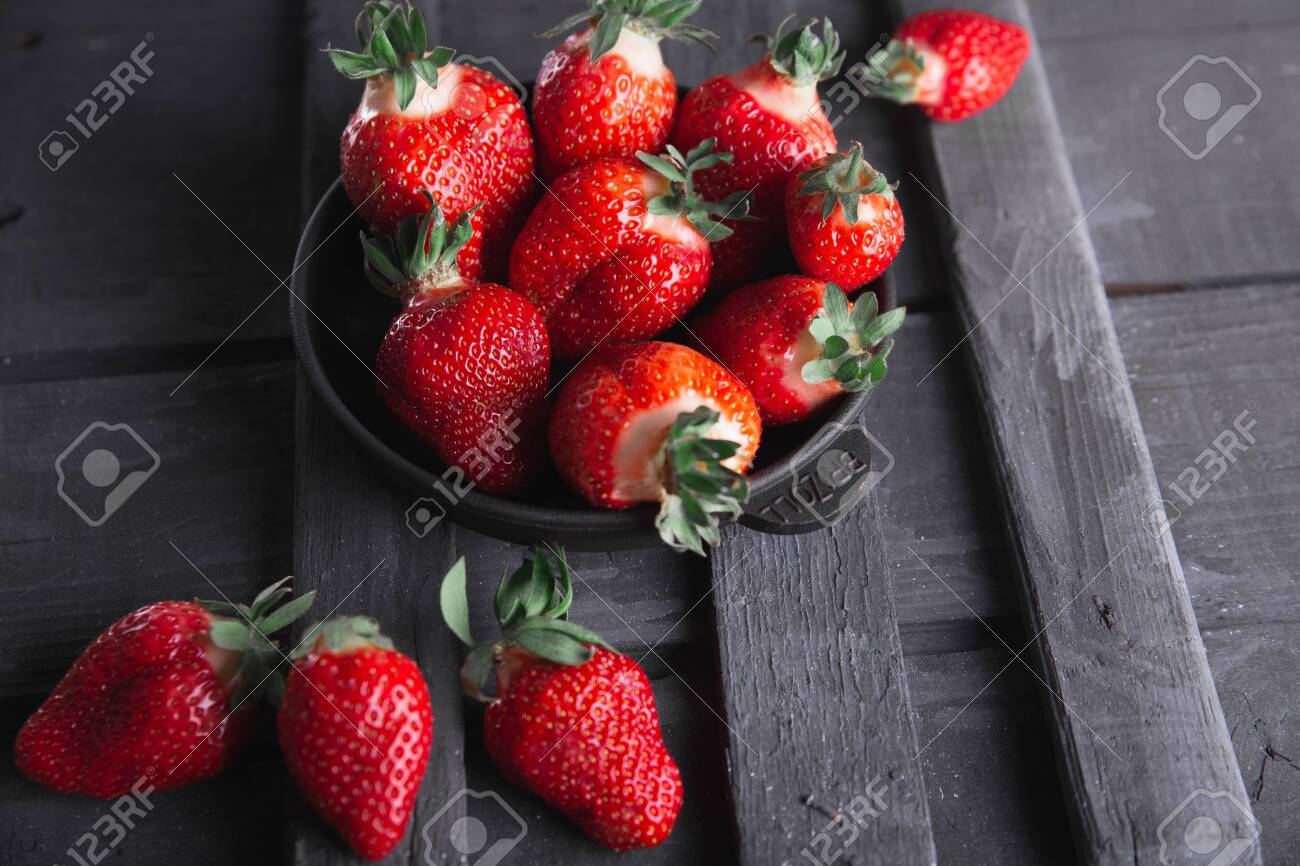 Fresh ripe strawberries on a black wooden background. - 154905664