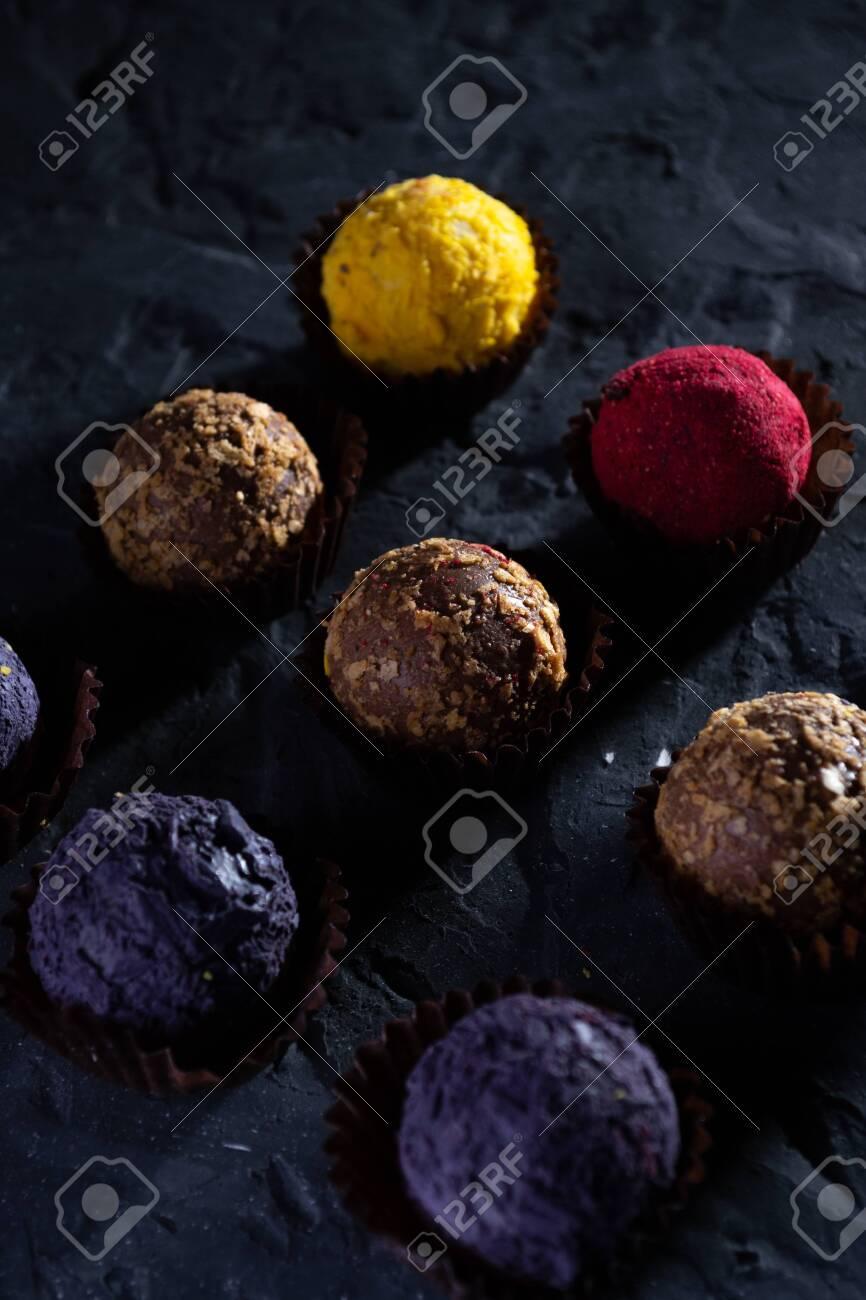 Colored round candies on a dark background. - 154905294
