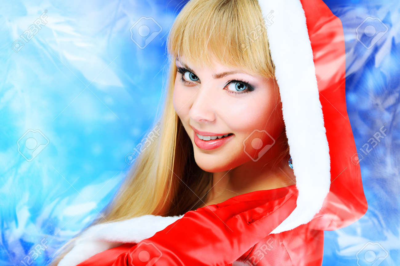 Portrait of a beautiful young woman wearing christmas clothes over sky of stars and snow. Stock Photo - 5889165