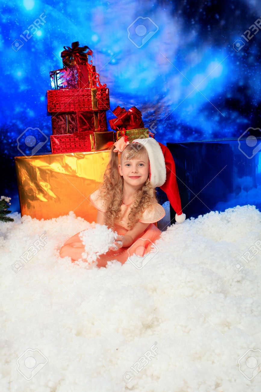 Christmas kid in Santa hat sitting in snowdrift. Stock Photo - 6098045