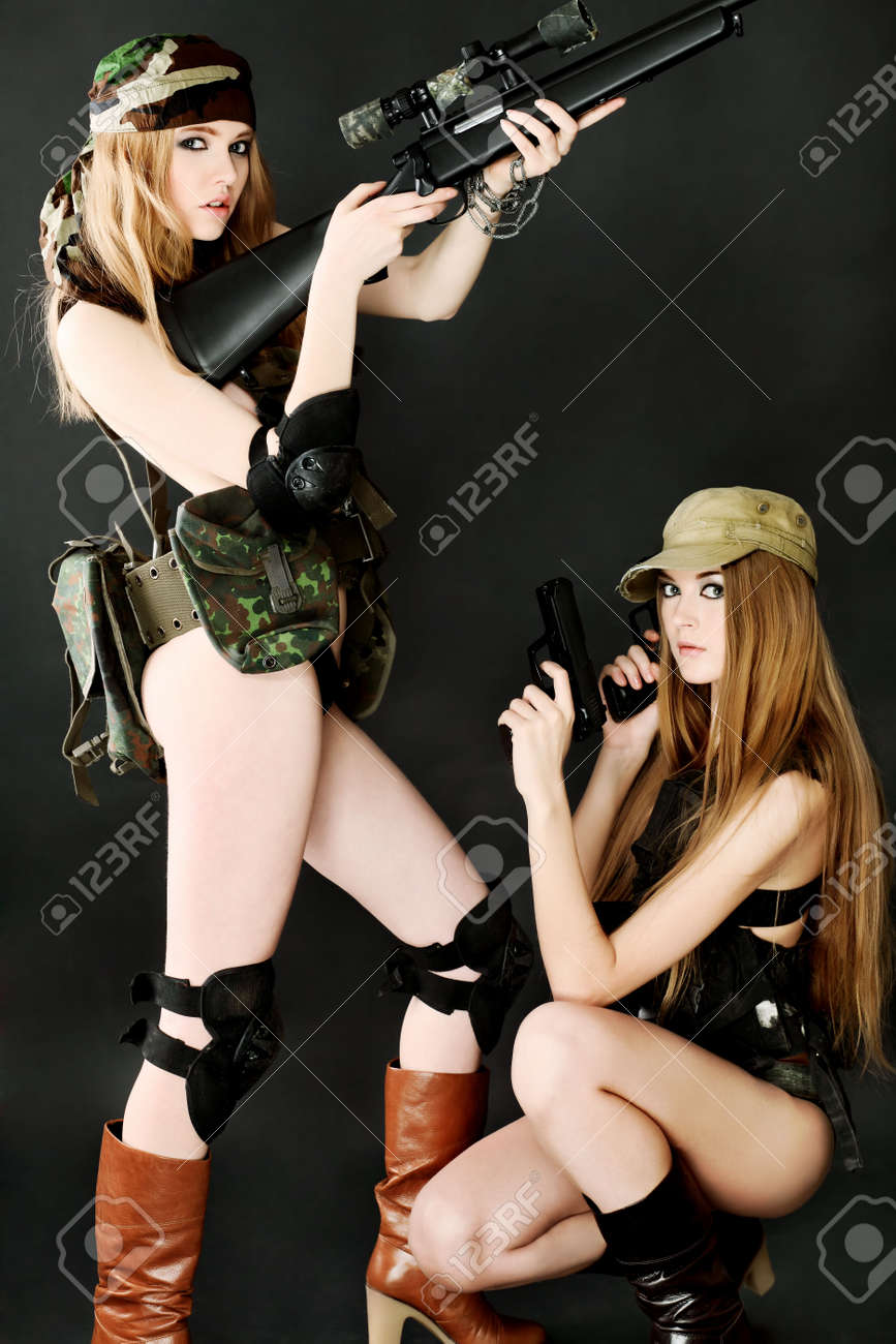 Two sexy women in military uniform posing against black background. Stock Photo - 6560309