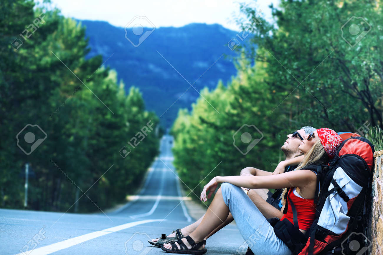 Pretty young woman tourist hitchhiking along a road. Stock Photo - 7498999