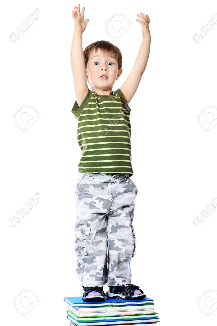 Portrait of a cute little boy standing on books. Isolated over white background. Stock Photo - 7552359