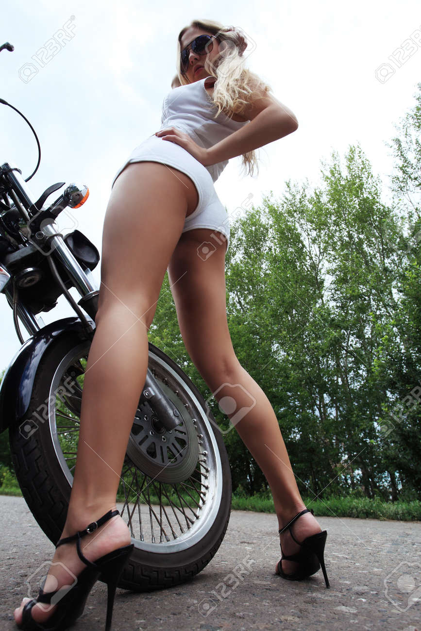 Shot of an attractive woman biker posing on her motorcycle. Stock Photo - 7647692