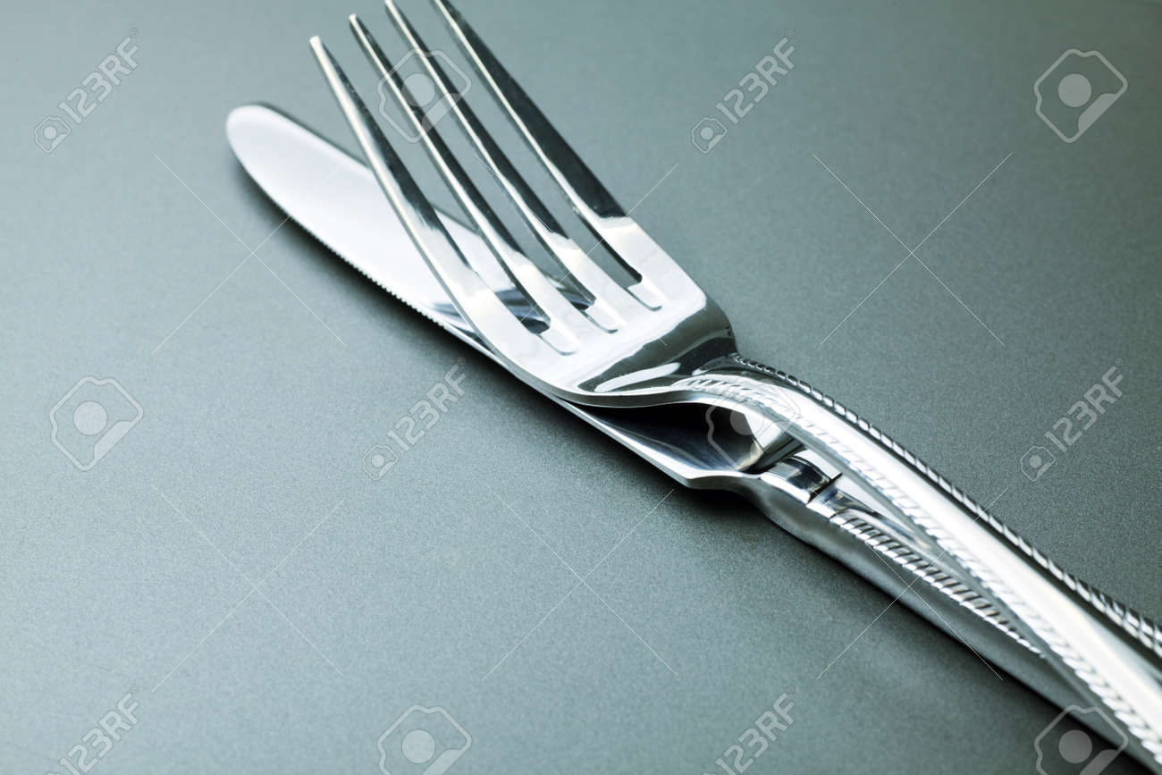 Silver fork, knife and spoon  over grey background. Stock Photo - 7803197