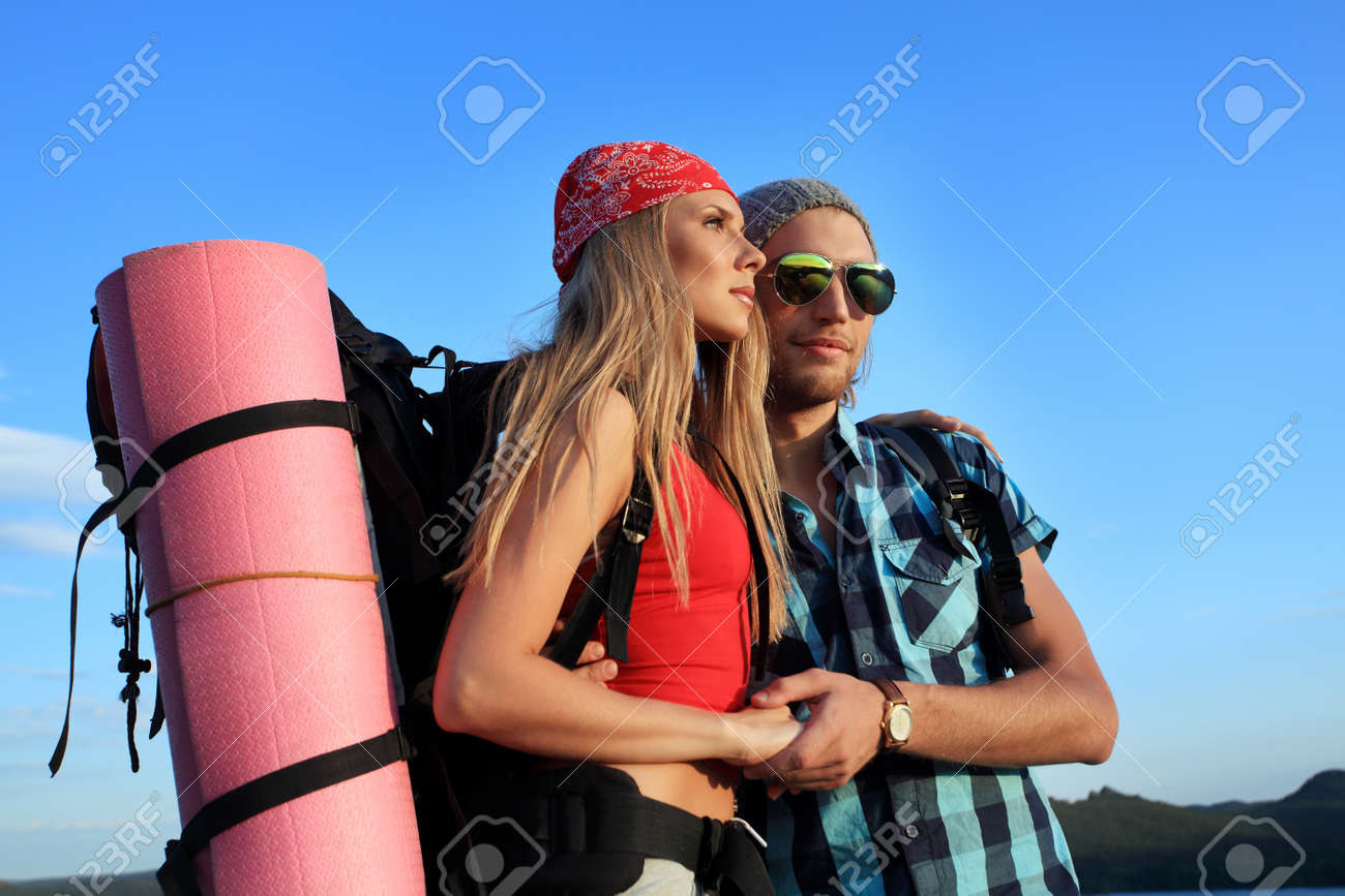 Couple of tourists are standing at the top of a mountain with a feeling of freedom. Stock Photo - 7907217
