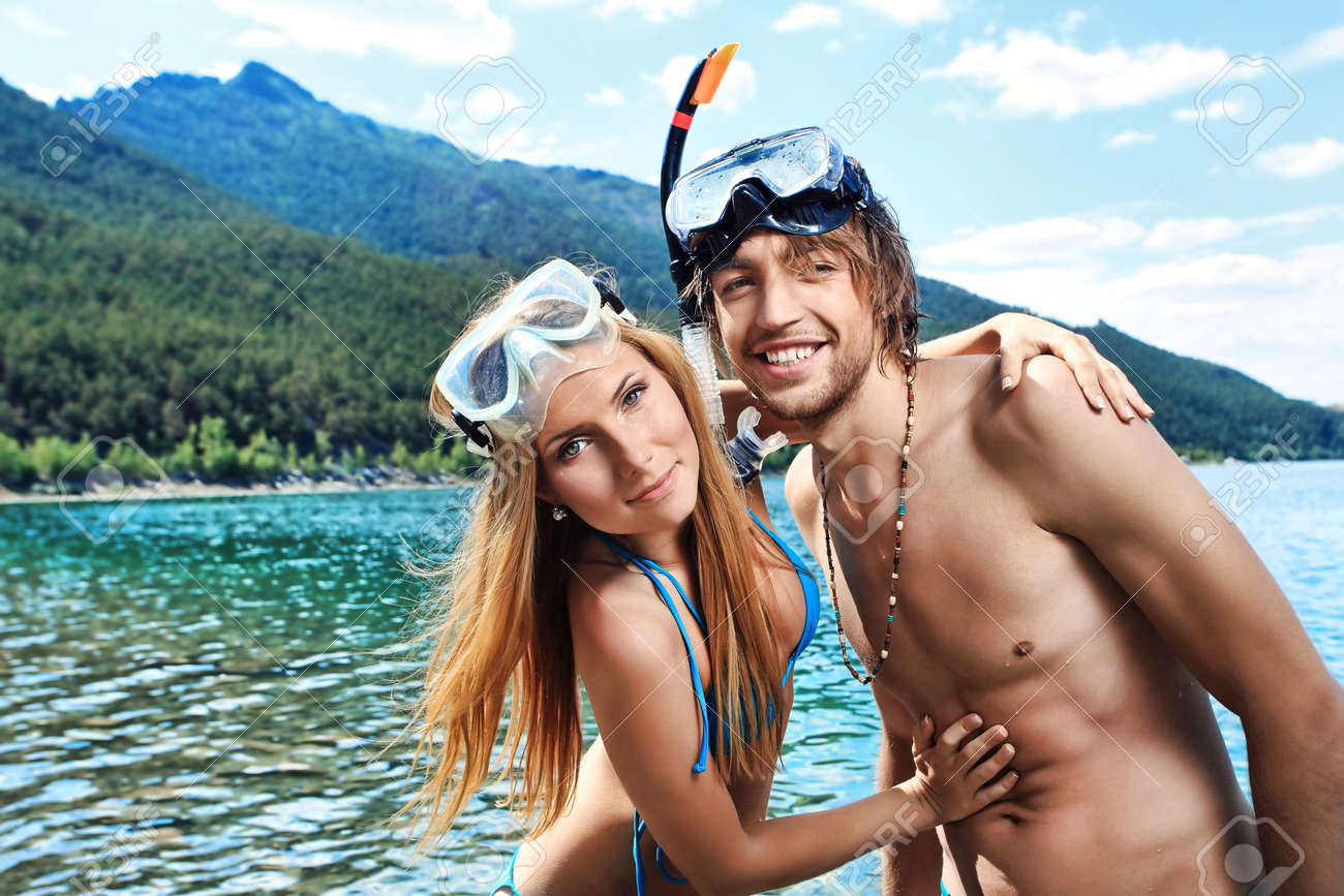 Happy young couple with snorkelling gear standing on a sea beach. Stock Photo - 7907314