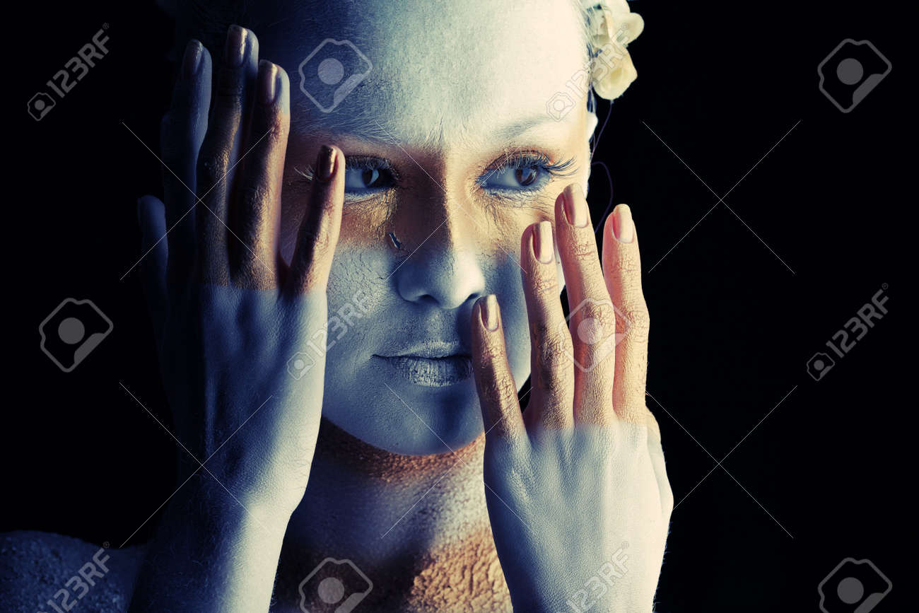 Portrait of an artistic woman painted with white and bronze colors, over black background. Body painting project. Stock Photo - 7992425