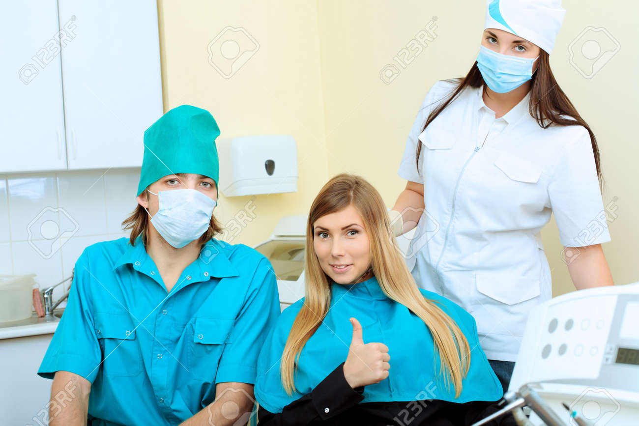 Shot of a young woman with dentists in a dental surgery. Healthcare, medicine. Stock Photo - 8088237