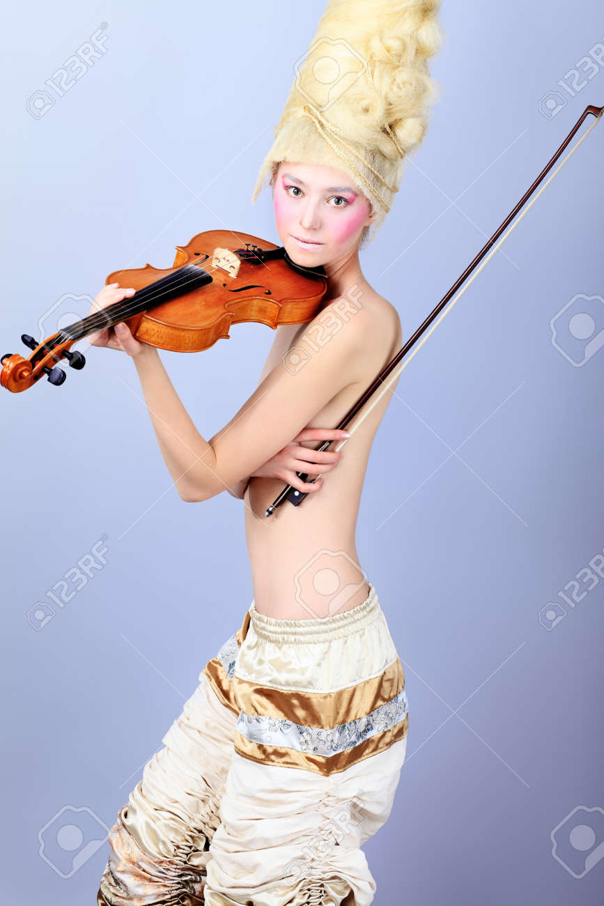 Portrait of an artistic young woman posing with violin. Shot in a studio. Stock Photo - 8108087