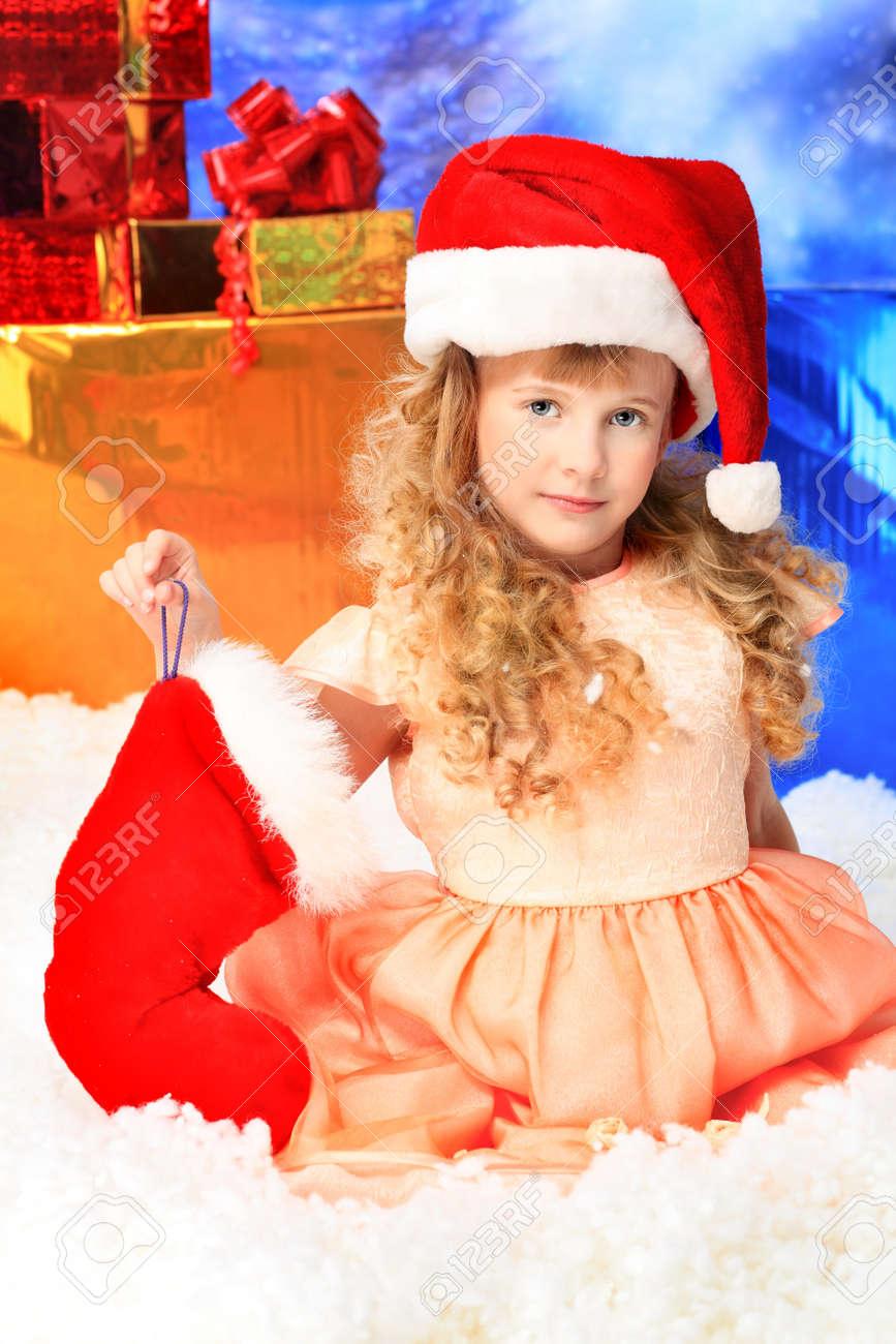 Christmas kid in Santa hat sitting in snowdrift. Stock Photo - 8108113