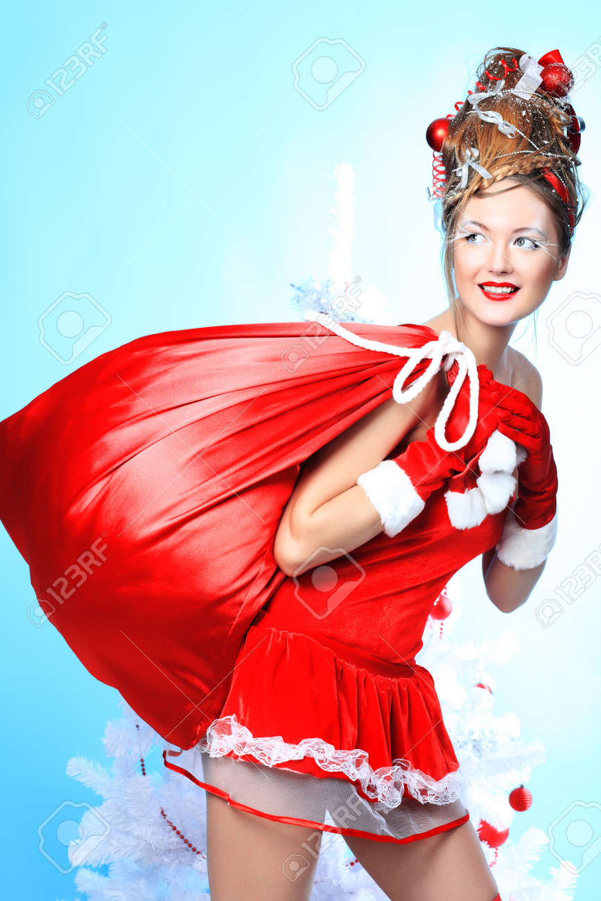 Beautiful young woman in Santa Claus clothes holding presents over Christmas background. Stock Photo - 8160244