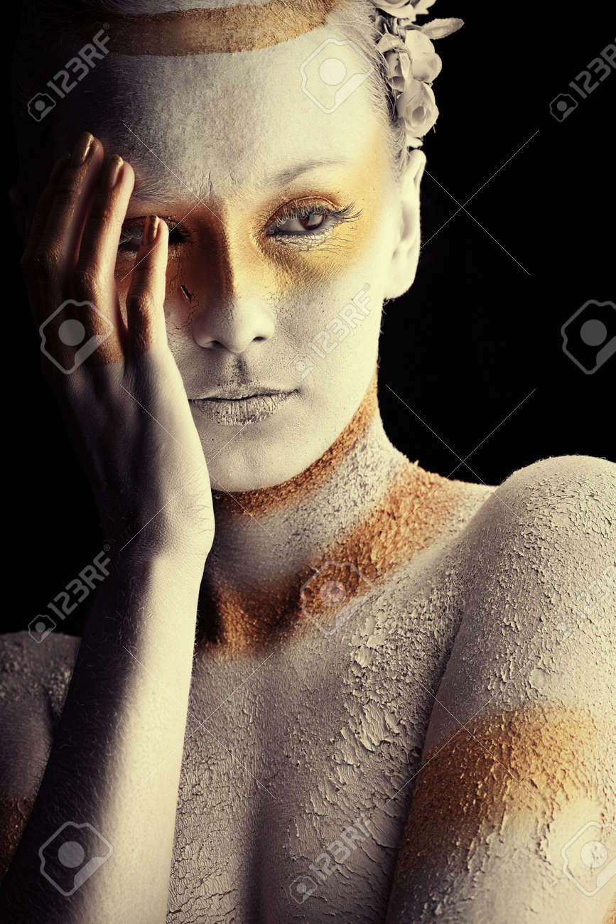 Portrait of an artistic woman painted with white and bronze colors, over black background. Body painting project. Stock Photo - 8217395