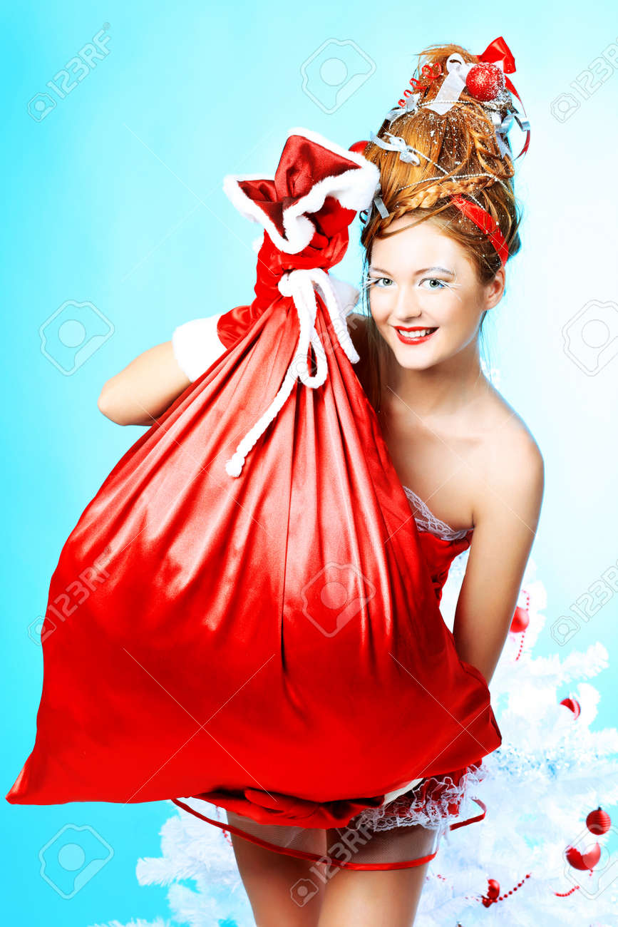 Beautiful young woman in Santa Claus clothes holding presents over Christmas background. Stock Photo - 8312962