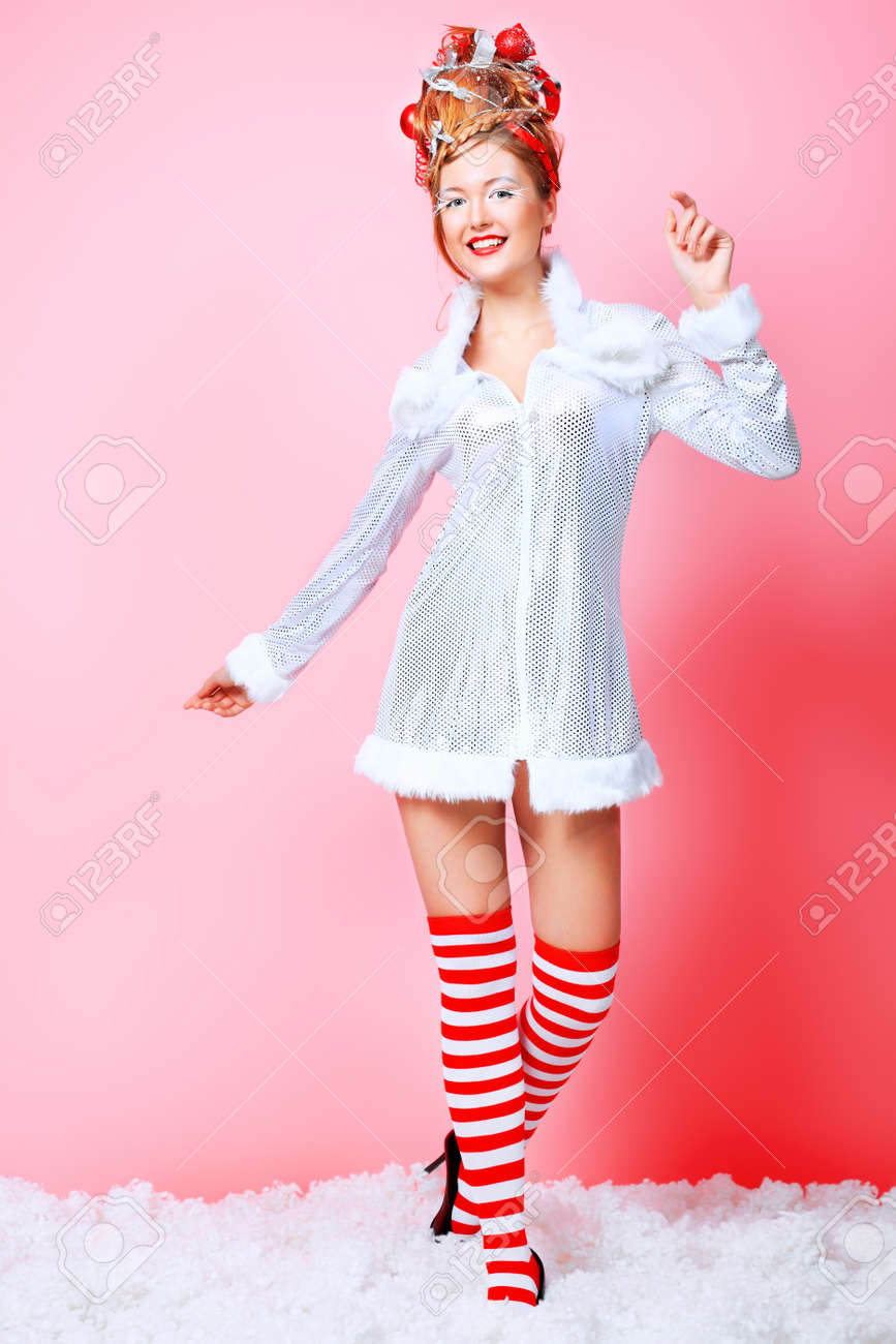 Fashionable young woman in Christmas clothes over pink background. Stock Photo - 8312930