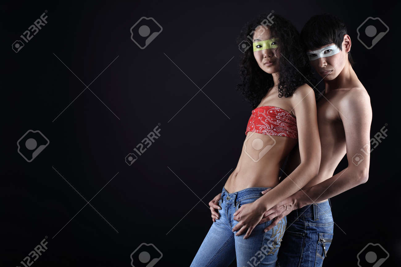 Shot of a couple of young people with painted eyes posing together over black background. Stock Photo - 8318896