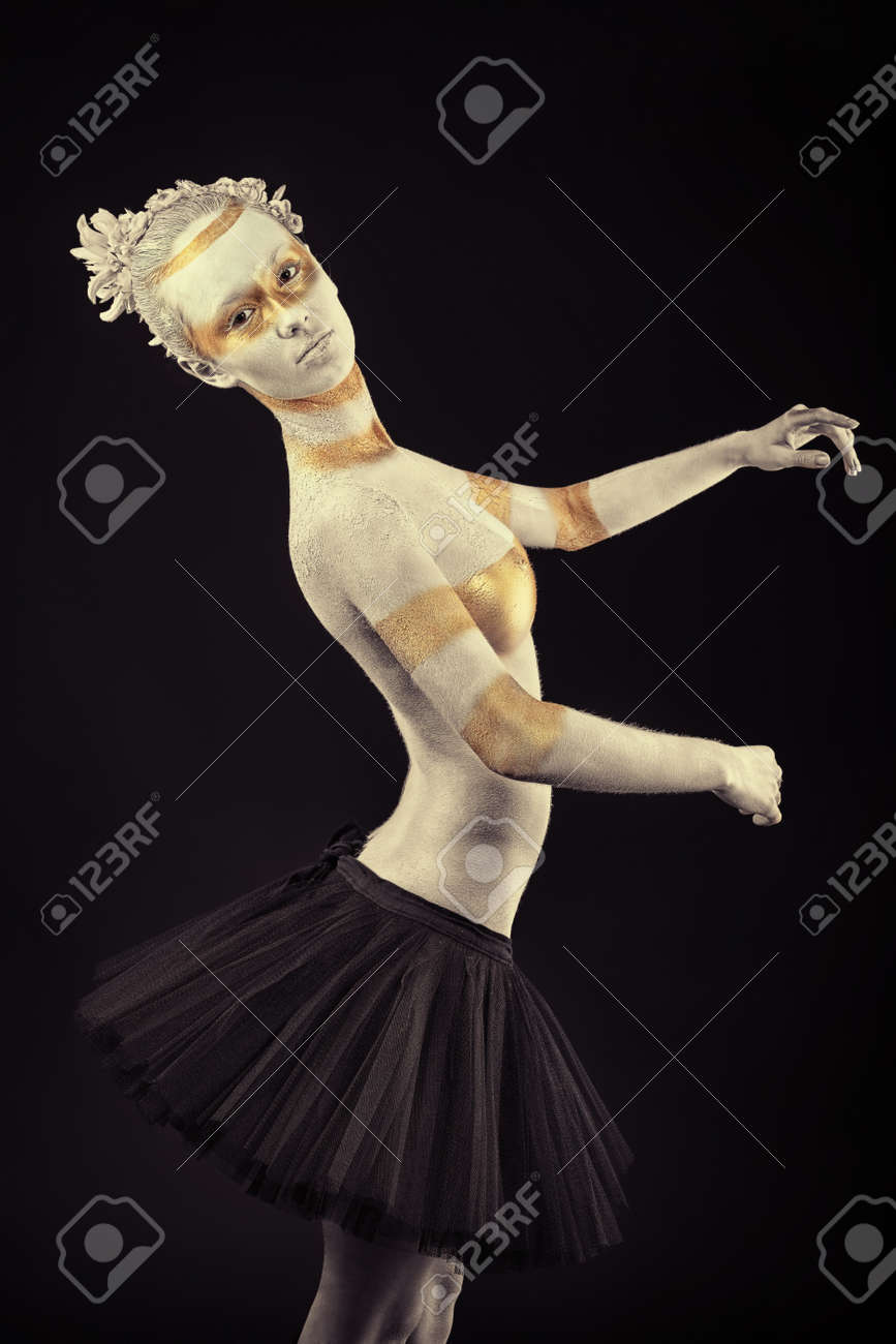 Artistic woman painted with  white and bronze colors, over black background. Body painting project. Stock Photo - 8318911