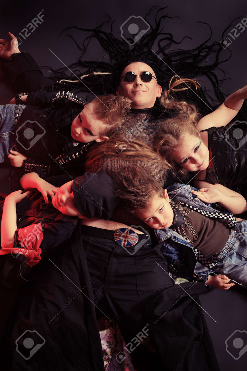 Heavy metal musician  with children lying on a floor. Shot in a studio. Stock Photo - 8646636