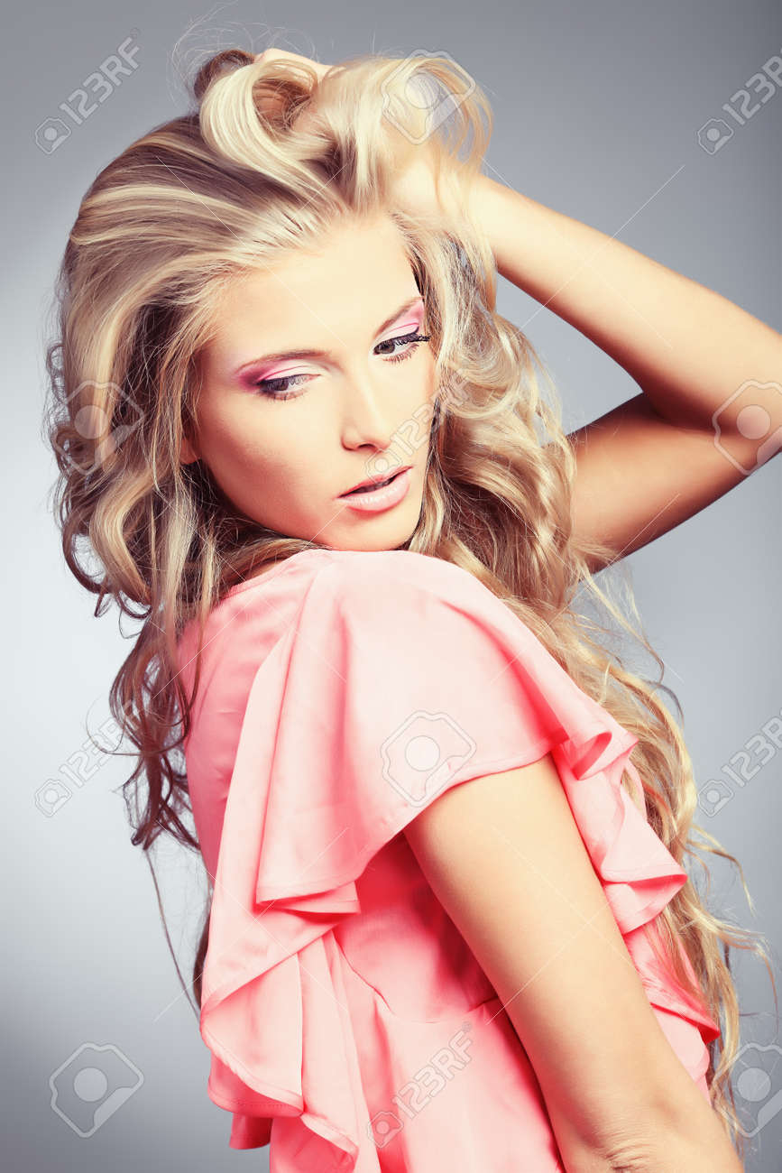 Beautiful young woman with long blonde hair posing over grey background. Stock Photo - 8714144