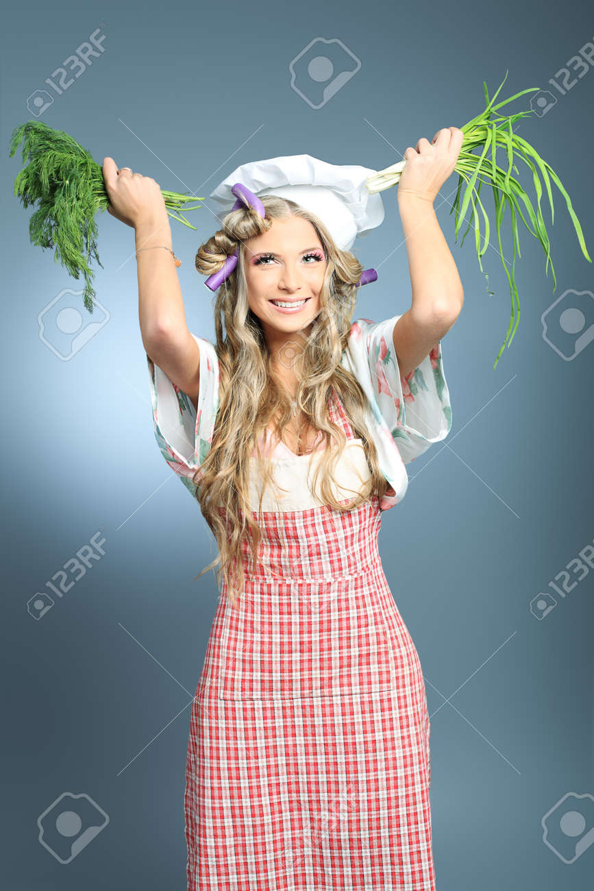 Beautiful blonde woman housewife holding greens and fruits. Studio shot over grey background. Stock Photo - 8714131