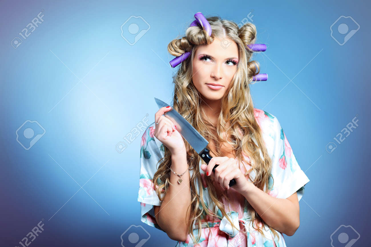 Portrait of a pretty girl with curlers in her hair holding a knife. Over grey background. Stock Photo - 8835174